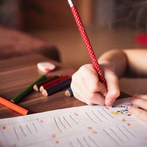 Bambina di profilo scrive su un quaderno con una matita rossa