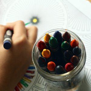 Pastelli a cera e una mano di bambina che colora