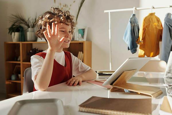 Bambina sorride ad un tablet e saluta