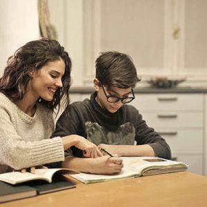 Ragazza aiuta un alunno a fare i compiti