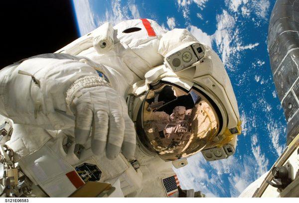 Astronauta con la Terra sullo sfondo. Lezioni di scienze con la Fucina dei Cervelli.